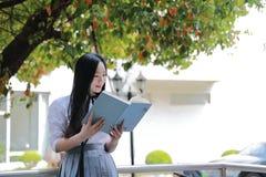 在学校阅读书的愉快的亚洲中国俏丽的女孩穿戴学生衣服本质上在春天 免版税库存图片