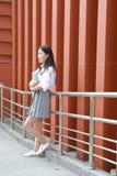 在学校阅读书的愉快的亚洲中国俏丽的女孩穿戴学生衣服本质上在春天 免版税库存照片