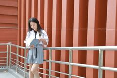 在学校阅读书的愉快的亚洲中国俏丽的女孩穿戴学生衣服本质上在春天 库存图片