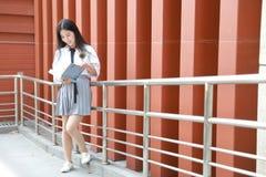 在学校阅读书的愉快的亚洲中国俏丽的女孩穿戴学生衣服本质上在春天 库存照片