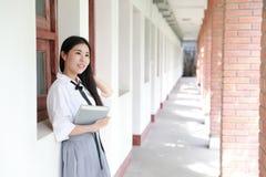 在学校阅读书的愉快的亚洲中国俏丽的女孩穿戴学生衣服本质上在春天 图库摄影