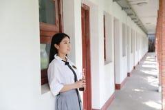 在学校饮用的可乐的愉快的亚洲中国俏丽的女孩穿戴学生衣服本质上在春天 库存图片