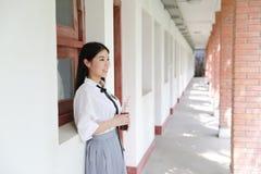 在学校饮用的可乐的愉快的亚洲中国俏丽的女孩穿戴学生衣服本质上在春天 免版税库存照片