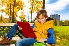 在学校以后的男孩在公园 免版税图库摄影