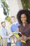 在学院校园里的微笑的女学生 免版税库存图片