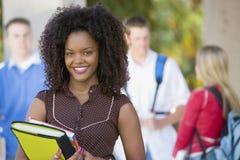 在学院校园里的微笑的女学生 免版税图库摄影