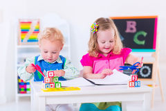 在学龄前绘画的愉快的孩子 库存照片