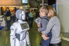 在孩子和机器人之间的一次活泼和有趣的交谈 免版税库存照片