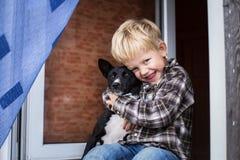 在孩子和他的宠物之间的爱 Basenji和男孩 免版税库存图片