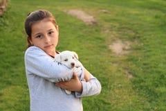 在孩子手上holded的小狗 免版税图库摄影