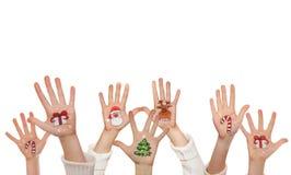 在孩子的手上绘的圣诞节标志 圣诞老人,雪人,圣诞树,当前箱子 免版税库存图片