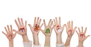 在孩子的手上绘的圣诞节标志 圣诞老人,雪人,圣诞树,当前箱子 免版税库存照片