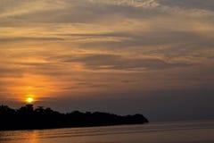 在它上的橙色天空与令人敬畏的在安静的太阳金黄反射挥动作为背景 在海滩的惊人的夏天日落视图 库存照片