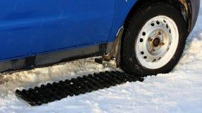 在它在a后,被困住长方形形状的黑防滑的席子被安置在一辆低成水平的汽车的轮子下 免版税库存照片