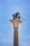 在它的专栏的飞过的圣马克狮子威尼斯标志。意大利。 库存照片