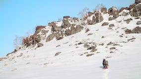 在它的脚的一个大积雪的山坡一个小组旅客,他们准备爬上 股票视频