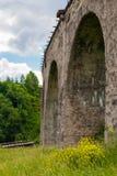 在它附近的老奥地利石铁路桥viaductand自行车 库存图片