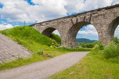 在它附近的老奥地利石铁路桥viaductand自行车 库存照片