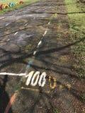 在守旧派体育场的被发射的沥青轨道 标号被绘 跑100米距离 库存照片