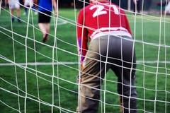 在守门员后的目标网红色制服的 大家踢橄榄球 免版税库存图片