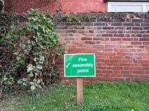 在安全之外的绿色火集合点木路标 免版税库存图片