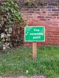 在安全之外的绿色火集合点木路标 免版税图库摄影