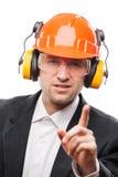 在安全安全帽盔甲的商人打手势感叹号的 库存图片