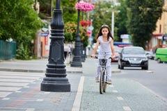 在安全帽的骑自行车逗人喜爱的孩子户外 红色自行车健康学龄前儿童夏天活动的小女孩 库存照片