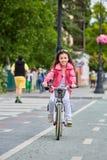 在安全帽的骑自行车逗人喜爱的孩子户外 红色自行车健康学龄前儿童夏天活动的小女孩 免版税库存照片