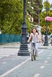 在安全帽的骑自行车逗人喜爱的孩子户外 红色自行车健康学龄前儿童夏天活动的小女孩 免版税库存图片