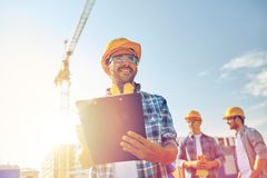 在安全帽的建造者有在建筑的剪贴板的 免版税库存图片
