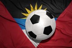 在安提瓜和巴布达国旗的黑白橄榄球球  库存图片