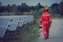 在安装太阳电池板的工程师工作;太阳能发电厂的操作由聪明的操作员的 库存照片