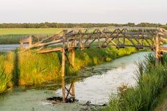 在安静的小河的木桥梁 免版税库存图片