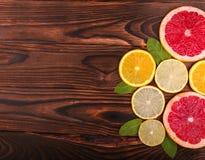 在完善的切片的一张顶视图在木背景的柑橘 鲜美葡萄柚和柠檬 明亮的桔子和绿色薄菏 免版税库存图片