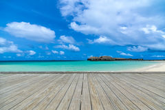 在完善的海滩的木灰色码头在与蓝天的晴天 免版税库存照片