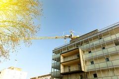 在完成的建造场所公寓buil上的黄色起重机 库存图片