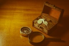 在宝物箱的硬币与指南针和放大镜 免版税库存照片