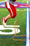 在实践的高中足球运动员跳跃的障碍 免版税库存图片