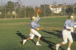 在实践,布伦特伍德,加州期间的少年联盟足球运动员传染性的橄榄球 免版税库存图片