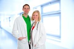 在实验室外套的友好的医疗队 免版税库存照片