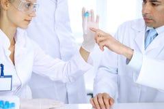在实验室学习物质或血样的科学研究员队  药理industr的新的疫苗 免版税库存图片