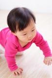 在客厅楼层上的爬行的女婴 免版税图库摄影