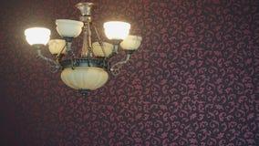 在客厅的一盏经典吊灯有红色墙纸的 免版税库存图片