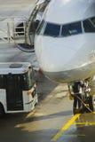 在客机的Tecnician工作在地面上的飞行前 库存照片