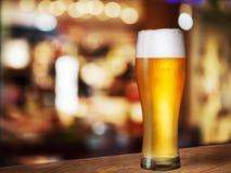 在客栈书桌上的冰镇啤酒玻璃 免版税库存图片