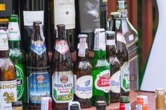 在客栈和餐馆的啤酒饮料进口的和地方品牌玻璃瓶 免版税图库摄影
