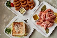在客栈或酒吧的啤酒快餐 虾、味道好的三明治和金黄洋葱圈 库存图片