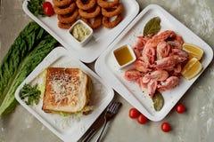 在客栈或酒吧的啤酒快餐 虾、味道好的三明治和金黄洋葱圈 图库摄影