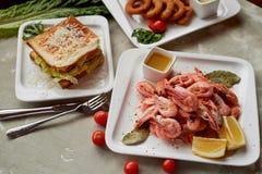 在客栈或酒吧的啤酒快餐 虾、味道好的三明治和金黄洋葱圈 免版税库存图片